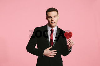 Handsome man in a black suit holding a red heart wearing a red tie