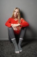 contented young woman sitting on floor in her room