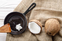 Coconut, shell with meat, cast iron skillet and spatula on hemp sackcloth on white wooden kitchen table