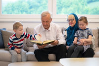 modern muslim grandparents with grandchildren reading Quran