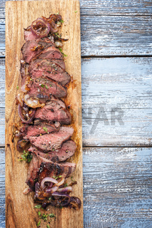 Traditional barbecue dry aged sliced roast beef with fried onion rings as top view on a wooden cutting board with copy space right