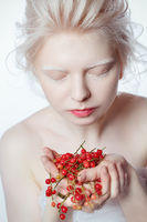 beautiful albino young woman with red berries