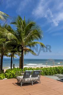 An outdoor rattan sofa on terrace facing the beach