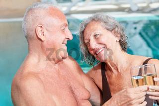 Senioren Paar feiert mit Sekt im Pool