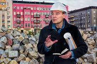 Bauleiter mit Notizbuch und Bauplänen schaut prüfend