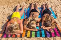 Three blonde girls sunbathing on beach