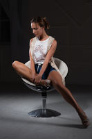 Pretty woman posing sitting on a chair.