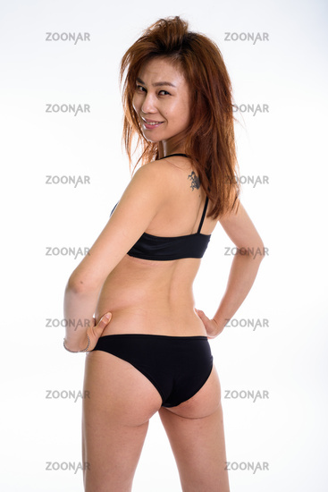 Studio shot of young happy Asian woman smiling and looking back