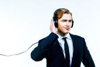 Man in suit smiling and listening to music on headphones