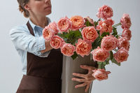 Girl florist with a big bouquet of pink roses around a gray background. The concept of a flower shop