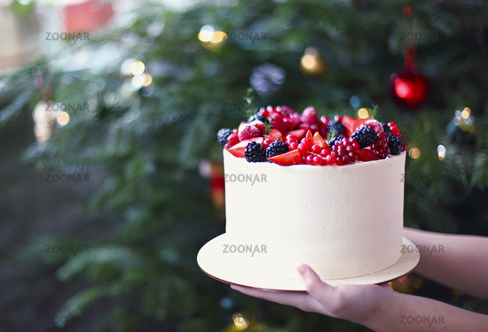 Woman holding Christmas Cake decorated with berries