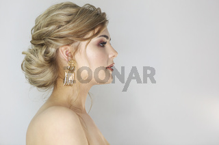 Portrait of the woman with fashion hairstyle and makeup wearing big golden earrings