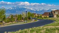Panorama Curving road and houses on a grassy hill overlooking the lake on a sunny day
