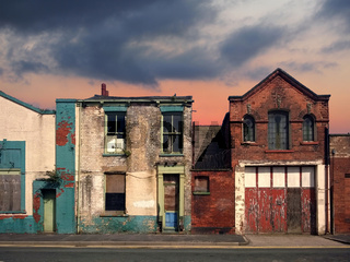 a deserted street of old abandoned ruined houses with bright peeling paint and crumbling brickwork in evening sunlight against a bright cloudy sunset sky