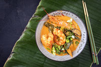 Traditional Thai kaeng phet red curry with king prawns and galgant as top view in a bowl on a banana leaf with copy space left
