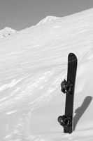 Snowboard in snowdrift after snowfall and mountains in background