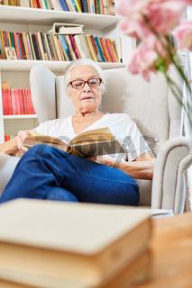 Senior Frau beim Lesen in einem Buch zuhause