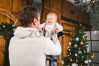 Man and cute baby are ready to celebrate new year. Happy Father And child son Near Christmas Tree And Fireplace In Christmas Evening. theme family holiday New Year and Christmas