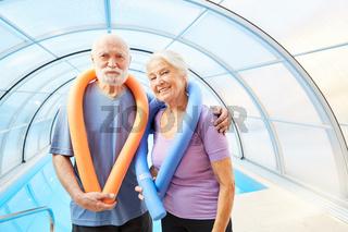 Glückliches Senioren Paar mit Schwimmnudeln