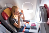 Woman drinking coffee on commercial passengers airplane during flight.