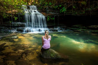 Woman enjoying nature. Dappled sunlight at the waterfall rock pool