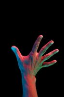 Bright fluorescent colorful hands isolated on a dark background. Close-up.