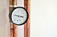 Closeup of pressure gauge connected to copper heating pipe.