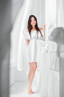 Young nice brunette dressed in a white dress.