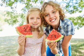 Geschwister Kinder mit leckeren Melonen