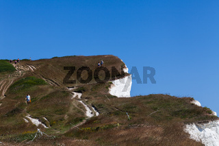 Young couple man woman walking down cliff surface. Two persons standing on rock enjoying summer holidays recreation. Sunny day background. Beach holidays
