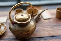 Copper teapot on a wooden table