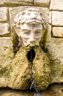 Ancient stone fountain. Fountain with head of man. The fountain's water comes out of the mouth of a