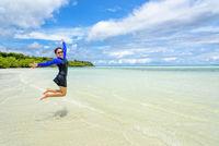 Happy asian teen girl jumping fun on the beach