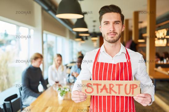 Junger Start-Up Gründer mit Schild im Restaurant