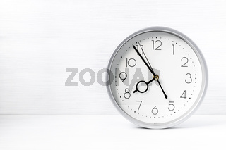 Silver wall clock on white wooden desk