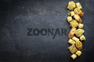 Traditional Oriental baklava collection as top view on a black board with copy space left
