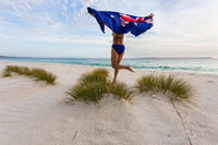 Woman running and leaping with Australian Flag