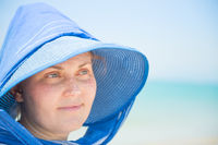 Woman in hat on blue water background