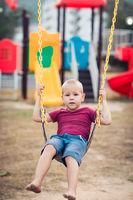 Little boy swinging on a swing
