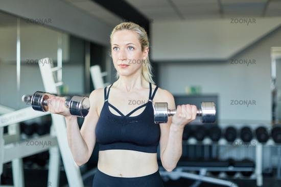 Junge Frau trainiert Bizeps Muskel mit Kurzhanteln