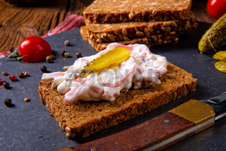 delicious spicy meat salad with cucumber on the black bread