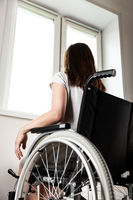 Invalid or disabled woman sitting wheelchair looking window daylight