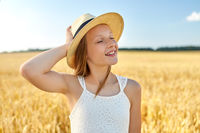 portrait of girl in straw hat on field in summer