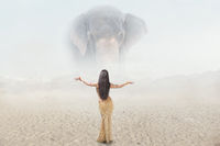 Fashion outdoor fantasy portrait of young woman in beautiful long dress posing in front of giant mirage elephant