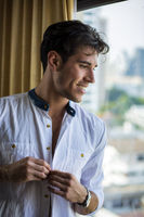 Sexy young man dressing by window curtains