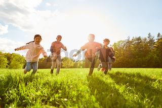 Kinder laufen und spielen auf einer Wiese