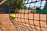 Yellow tennis ball in net