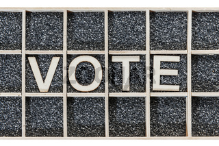 Wooden word VOTE on black sand