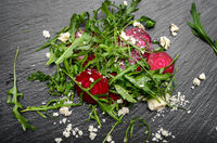 Beetroot arugula and feta cheese salad on slate stone plate closeup flat lay view