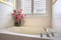 Home bathroom with a bathtub installed in front of the window with blinds
